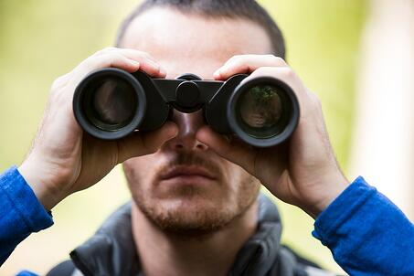 Close-up of male hiker looking through binoculars in forest.jpeg