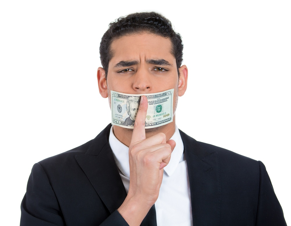 Closeup portrait of handsome corrupt guy in black suit with twenty dollar bill taped to mouth and showing shhh sign, isolated on white background. Bribery concept in politics, business, and diplomacy..jpeg