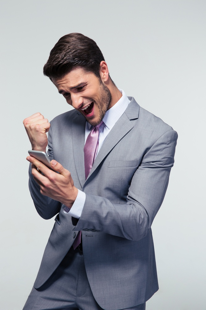 Happy businessman holding smartphone and celebrating his success over gray background.jpeg