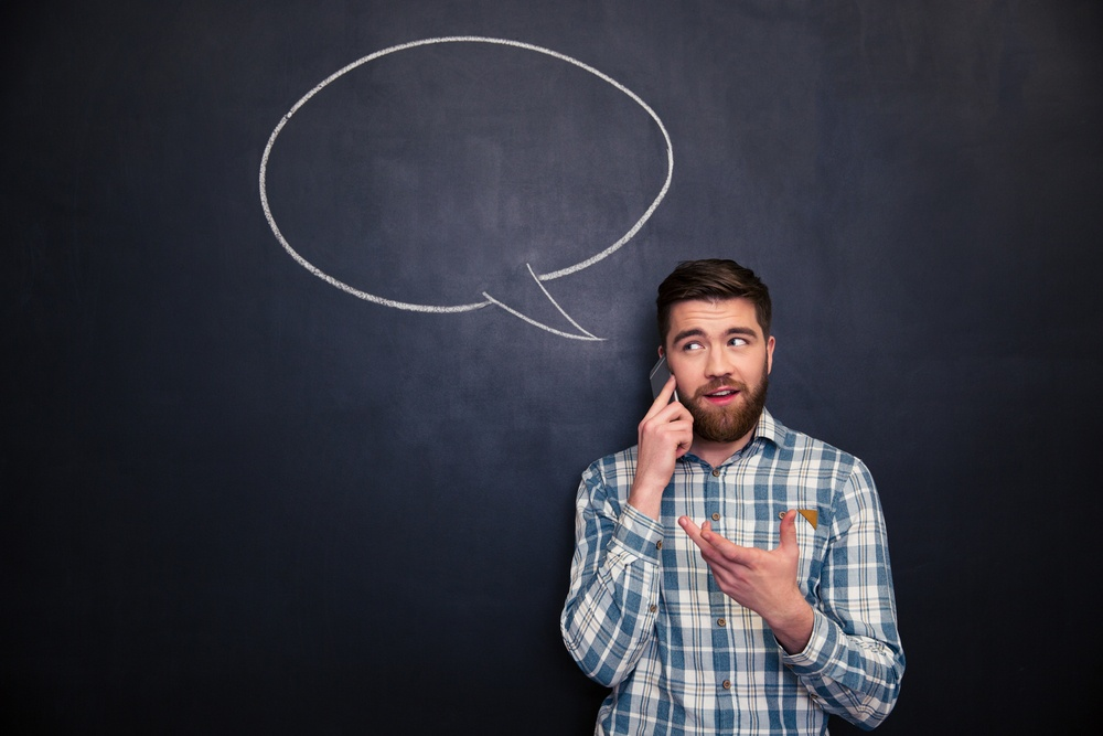 Happy handsome young man with beard talking on mobile phone standing over chalkboard background with blank speech bubble.jpeg